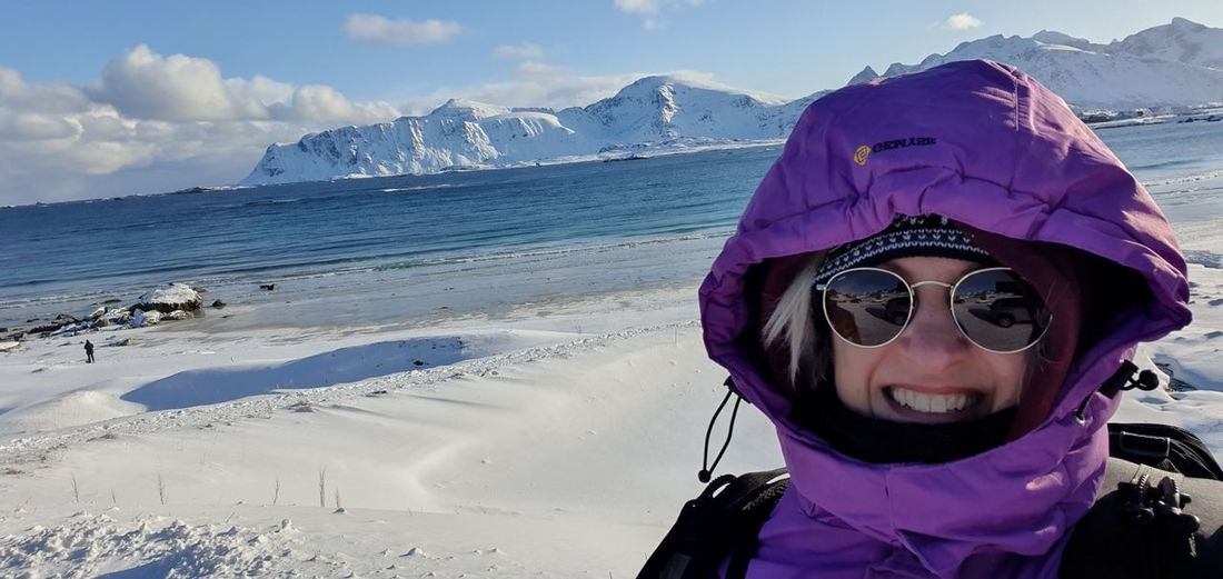 Portrait of woman against snowcapped mountains during winter