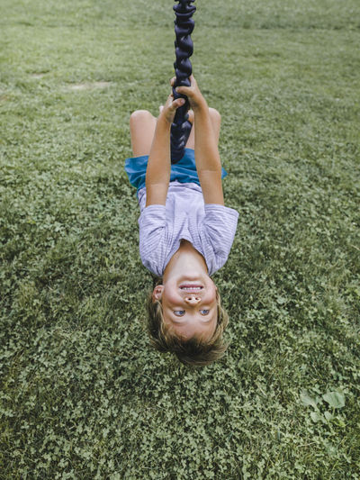 High angle view of boy on swing over grassy field