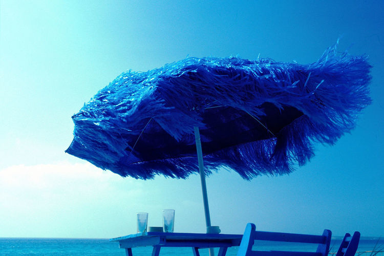 Beach Beach Umbrella Beauty In Nature Blue Blue Sky Clear Sky Day Horizon Horizon Over Water Low Angle View Motion Nature No People Outdoors Protection Sea Sky Thatched Roof Tranquil Scene Tranquility Umbrella Water Windy