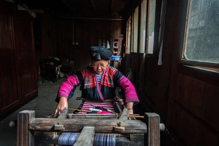 Mature woman weaving at workshop