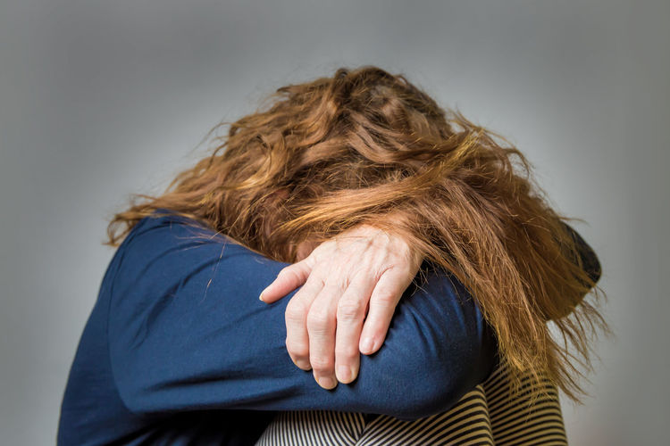 An unhappy woman hides her face Hair Redhead Hairstyle Adult Studio Shot Women Emotion Portrait Depression Depressed Sad Addiction Sadness Problems Loneliness Frustration Sitting Abuse Tired Illness Lonely Unhappy Stress HEAD