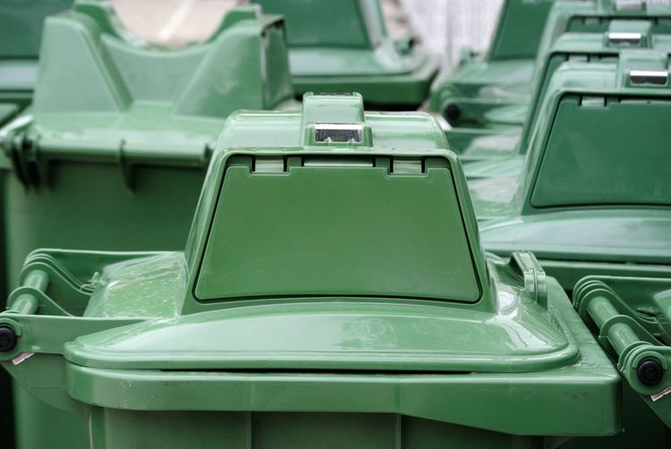 Close-up of green garbage bins