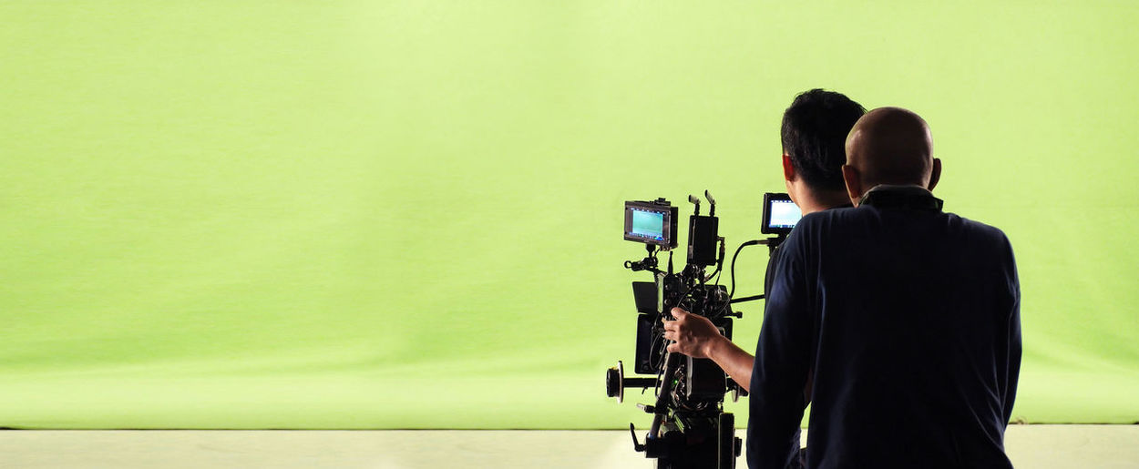 Camera and green screen studio in panorama view and man working or shooting or recording or filming. Crew Film Green Men Panorama People Production Rear View Screen Set Shooting Studio Team Video Video; Camera; Green; Screen; Studio; Production; Tv; Set; Film; Television; Stage; Media; Equipment; Movie; Background; Chroma; Broadcasting; Digital; Interview; Broadcast; Image; Professional; Technology; Photographer; Crew; Chromatic; Virtual; Lens; Pr Working
