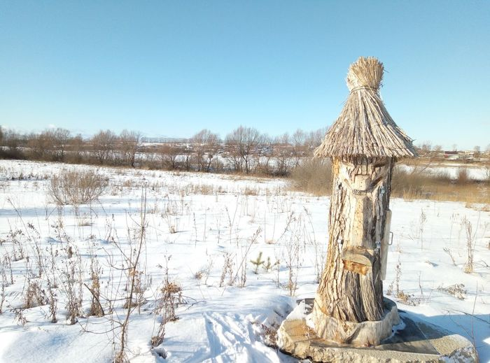 Snow covered land and beehive against clear sky during winter, folk taming beehives .