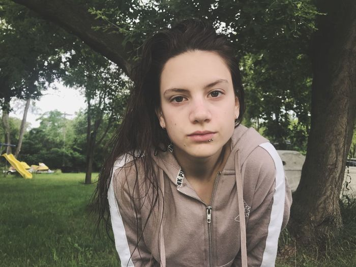 Portrait of young woman bending at park