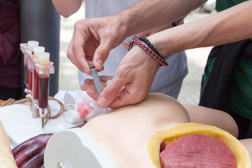 A student practicing on a manikin how to give an intramuscular injection. Care Doctor  Hands Healthcare Inject Injection Intramuscular Lesson Medical Procedure Medicine Nurse Blood Sample Blood Sample Tube Buttocks Education Flesh Health Healthcare And Medicine Injecting Manikin Medicine Students Muscular Practicing Syringe Training