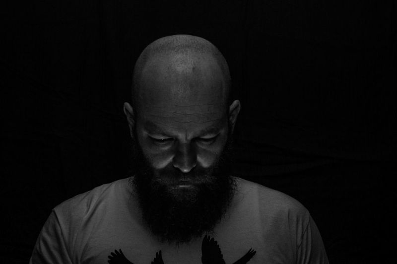 Close-up of bearded man against black background