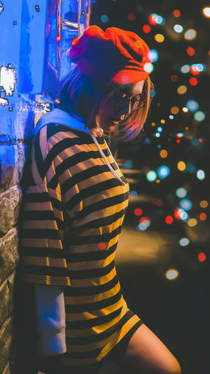 Photo of a woman wearing a striped pattern With bokeh as background One Person Illuminated Lifestyles Real People Women Celebration Leisure Activity Night Three Quarter Length Christmas Glowing Standing Looking Casual Clothing Child Childhood Indoors  Females Side View Hairstyle