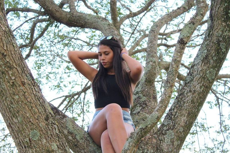 Low angle view of woman with hands in hair looking down while sitting on tree