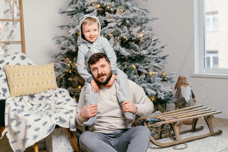 Full length of man sitting on christmas tree