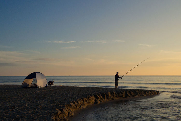 Side View Of Man Fishing In Sea At Sunset
