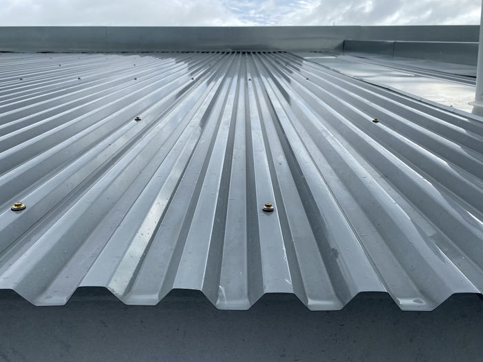 Close-up of metallic roof against sky