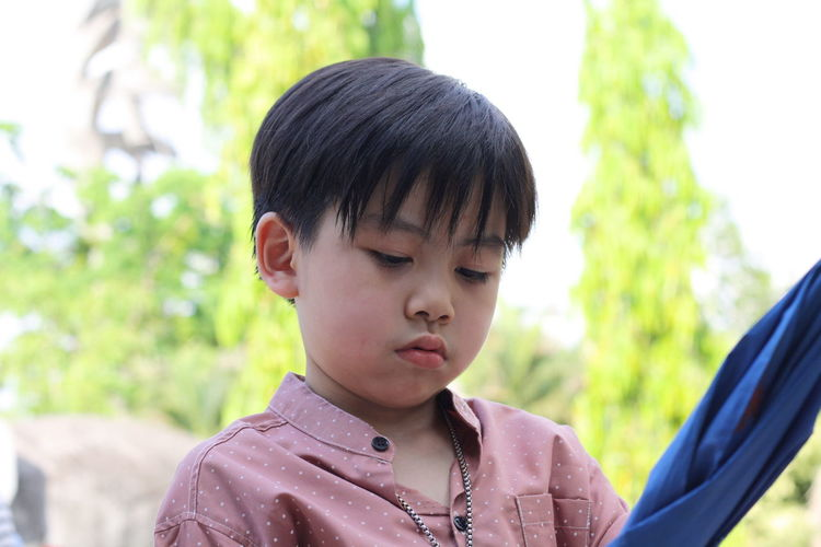 the boy touchy Childhood Child Headshot Portrait One Person Men Focus On Foreground Males  Boys Day Innocence Close-up Looking Casual Clothing Real People Front View Black Hair Outdoors Contemplation Hairstyle Asain Boy