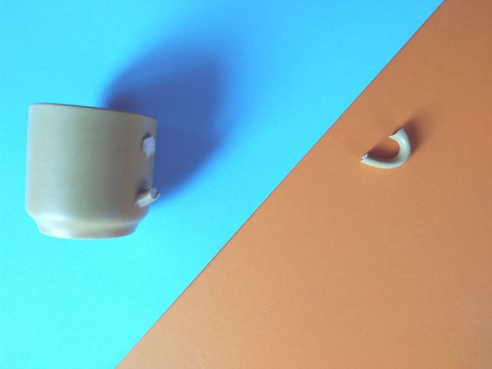 Close up of broken coffee mug against blue and orange background