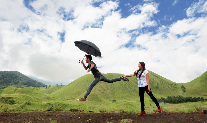 Woman Pulling Man Leg While Standing On Hill Against Cloudy Sky