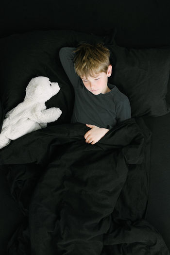 Child looking sad in black bad with stuffed toy polar bear Bed Berlin Black Boys Caucasian Child Depression European  Friends German Imaginary Imagination Indoors  Kids One Person People Polar Bear Sadness Sleeping Stuffed Animals Stuffed Toy Welcome To Black White