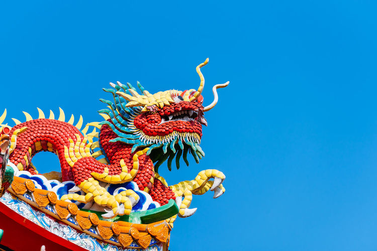 Chinese dragon statue on top of roof with blue sky background Chinese Dragon Dragon Multi Colored Blue Clear Sky Cultures Sculpture Chinese New Year Sky Statue