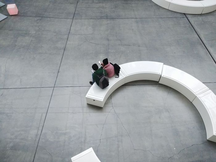 High angle view of people sitting on tiled floor