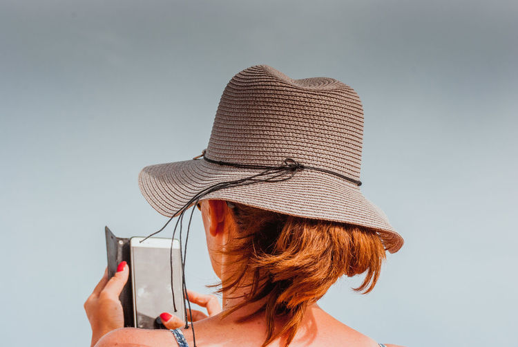 Adult Camera - Photographic Equipment Clear Sky Close-up Day Hat Headshot Holding Leisure Activity Lifestyles One Person One Woman Only Outdoors People Photographing Real People Rear View Sky Sun Hat Technology Women Young Adult