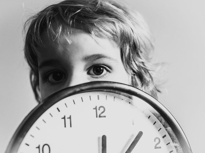 Portrait of boy with wall clock against white background