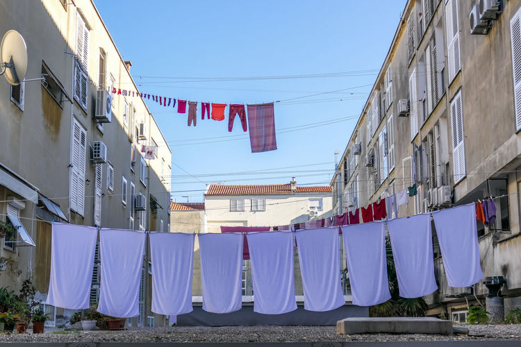Hanging Architecture Built Structure Building Exterior Drying Clothesline Flag No People Laundry Sky Nature Day Building Patriotism Clothing Side By Side Clear Sky Blue In A Row Textile Outdoors
