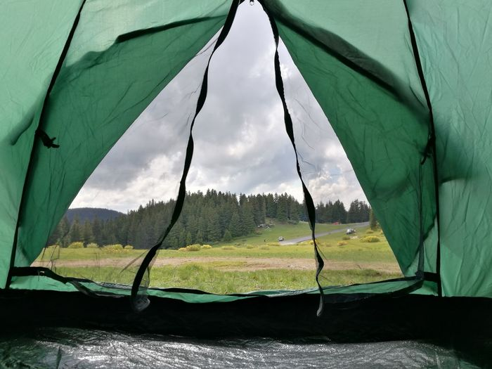 Scenic view of landscape seen through tent against sky