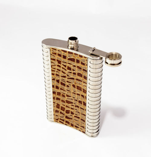 Decorative flask made of stainless steel decorated with crocodile skin on the sides on a white background Accessory Bottle Close-up Color Container Crocodile Decorative Design Flagon Flask Gift Hard Isolated Leather Liquor Metallic Personal Reptile Skin Souvenir Stainless Steel Stylish Travel White Background
