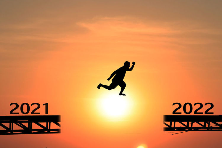 Silhouette people jumping against orange sky