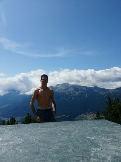 Shirtless man standing at granite by mountains against sky