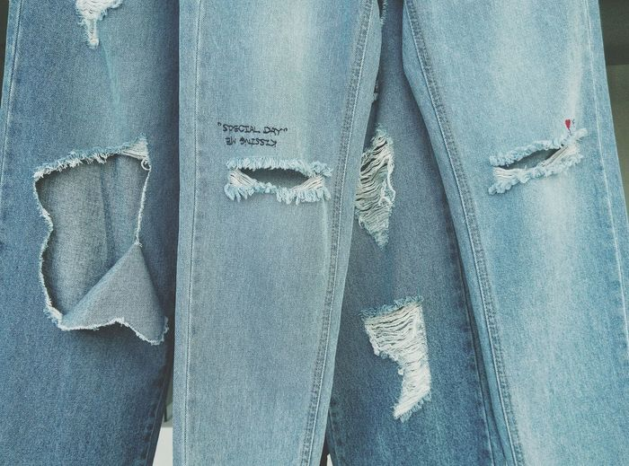 Close-up of torn jeans hanging in store