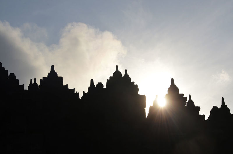 Low angle view of silhouette built structures against sky