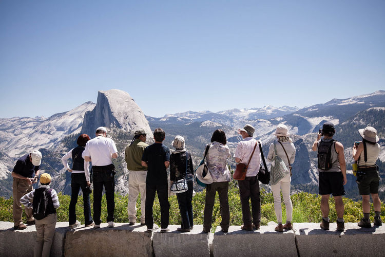 Rear View Of People Looking At Mountains Against Clear Blue Sky