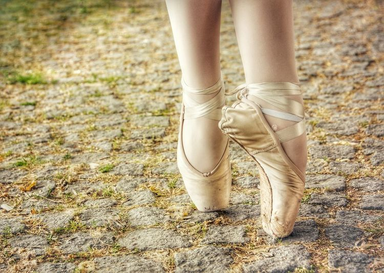 Low section of ballet dancer dancing on footpath