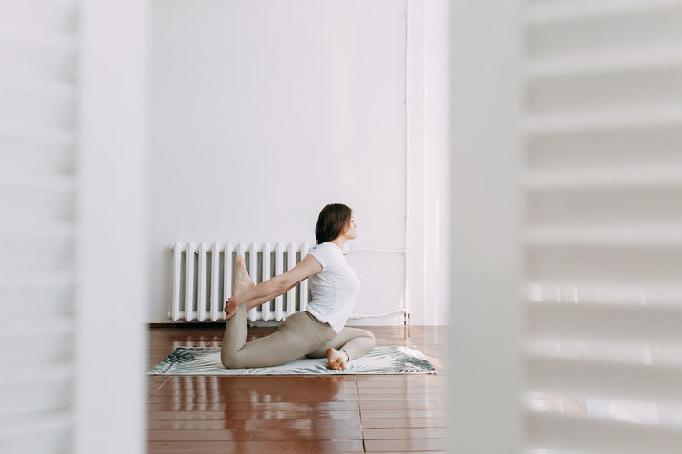 Side view of woman sitting on floor at home