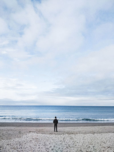 Rear view of man standing on shore at beach against cloudy sky