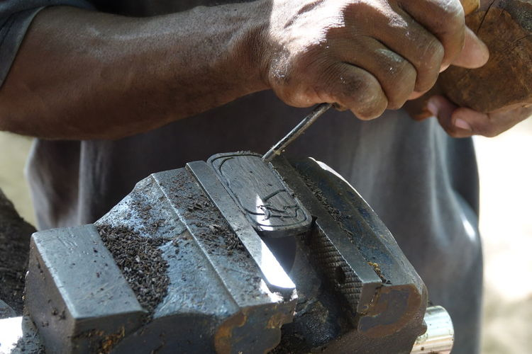 Midsection Of Worker Working On Metal