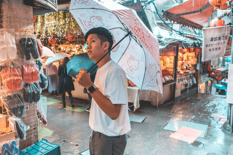 City Holding One Person Three Quarter Length Standing Real People Architecture Lifestyles City Life Casual Clothing Leisure Activity Incidental People Adult Market Young Adult Retail  Street Looking Outdoors Rain