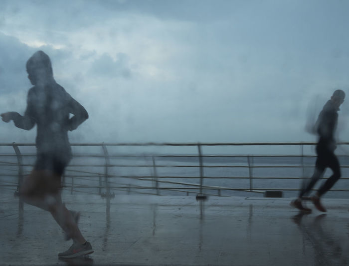 Blurred motion of people walking by sea against sky