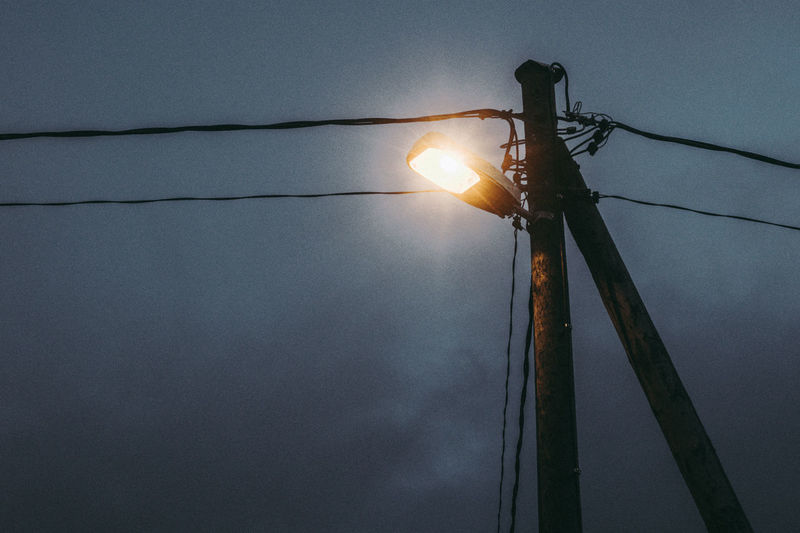 Low angle view of illuminated street light against sky