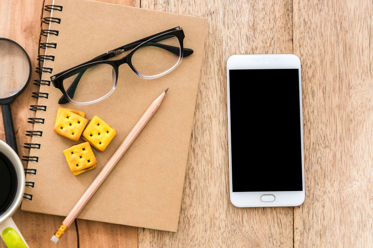 Directly above shot of mobile phone by eyeglasses and food on table