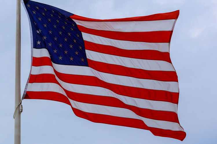 Close-Up Of American Flag Waving Against Sky