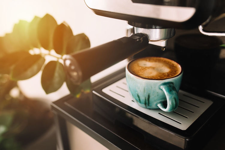 Green cup of coffee at the coffee maker machine, coffee time. blurred background. high quality photo
