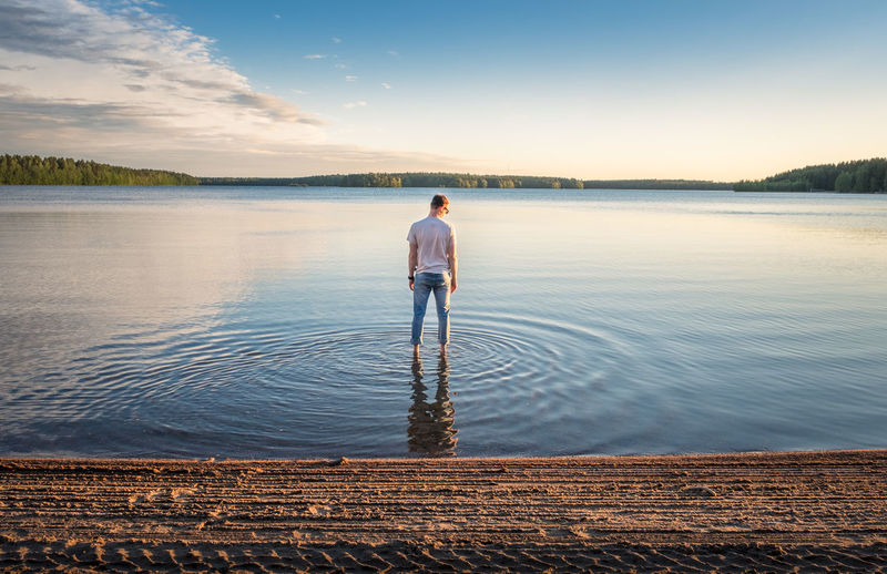 Man standing in water at beautiful summer day with idyllic lake and tranquil evening in Finland Water One Person Scenics - Nature Sky Rear View Standing Beauty In Nature Lake Nature Tranquility Tranquil Scene Real People Reflection Leisure Activity Idyllic Lifestyles Beach Outdoors Looking At View Day Summer Finland Tranquility Evening Light Atmospheric Mood