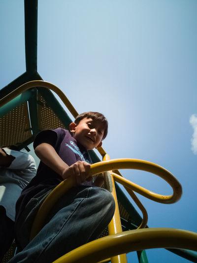 Portrait of boy sitting against sky