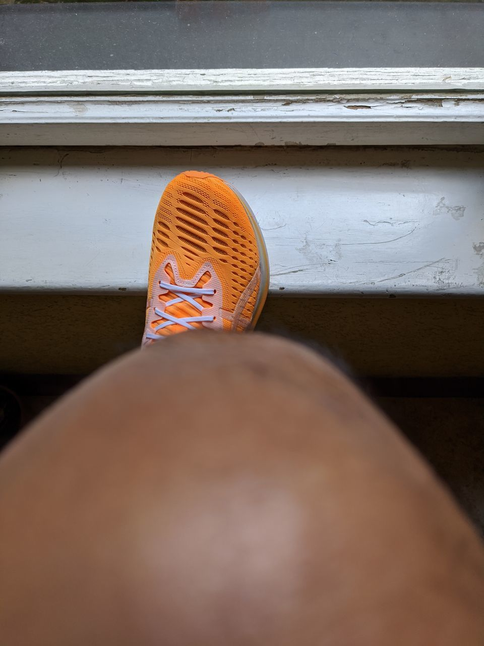 LOW SECTION OF PERSON WEARING SHOES ON WINDOW