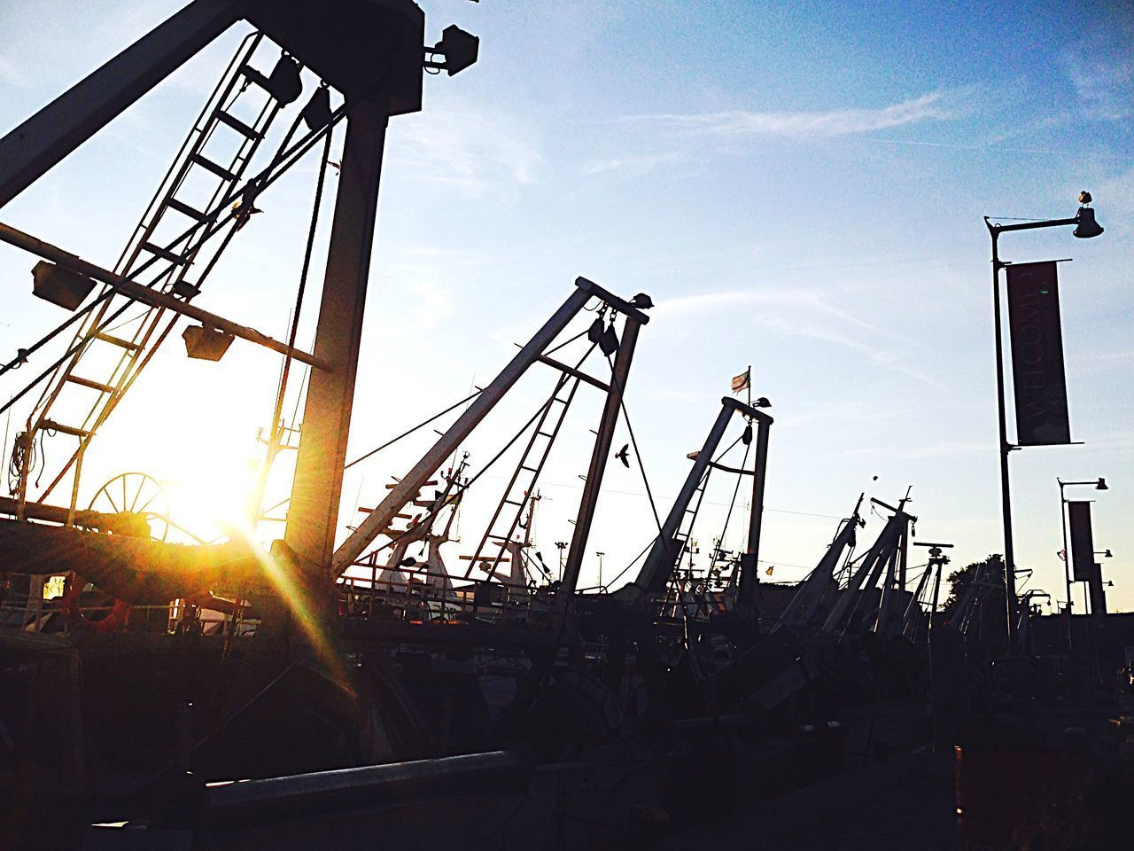 sunlight, sky, back lit, built structure, sunset, outdoors, no people, rollercoaster, amusement park, architecture, day