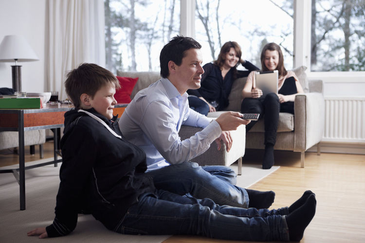 Rear view of people sitting on floor