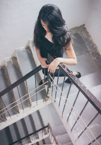 High Angle View Of Woman Standing On Staircase