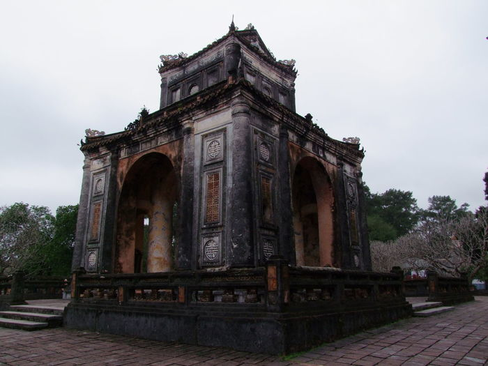 Tu Duc Tomb Arch Architecture Building Exterior Built Structure Composition Culture Dilapidated Façade Famous Place History Huế Low Angle View No People Ornate Outdoor Photography Outdoors Pillars Place Of Worship Religion Spirituality Traditional Trees Tu Duc Tomb Vietnam White Clouds
