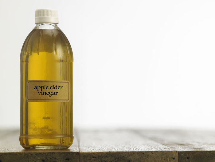 apple cider vinegar on the wooden table top Cooking Food And Drink Liquid Natural Acetic Apple Cider Vinegar Bottle Clear Close-up Condiment Container Copy Space Food Glass - Material Indoors  Ingredient Label No People Savory Food Studio Shot Table Top Taste Text Transparent White Vinegar